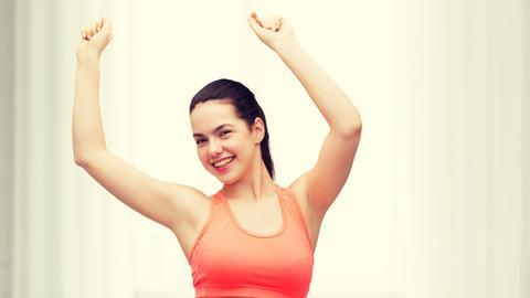 Frau im Fitness-Outfit hat die Arme in die Luft gestreckt.