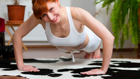Eine Frau macht in einer Wohnung eine Rückenübung.