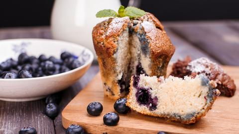 Ein aufgeschnittener Muffin mit Zucker-Zimt-Mischung und Blaubeeren.