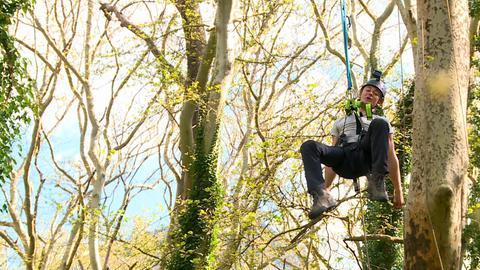 Jugendliche lässt sich auf einer gigantischen Schaukel zwischen Bäumen hinab schwingen.