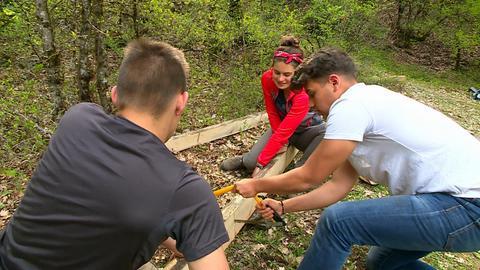 Drei Jugendliche zersägen einen Holzbalken.