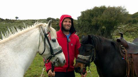 Coach Tobi, lächelnd, mit zwei Pferden.