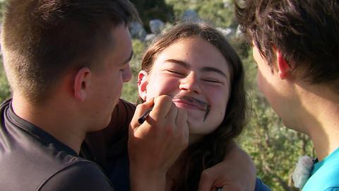 Ein Jugendlicher malt einer Jugendlichen einen Schnurrbart ins Gesicht. Sie schmunzelt mit zusammengekniffenen Augen.