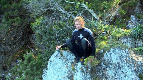 Jugendliche sitzt an einem Felsabhang und schaut skeptisch hinunter.