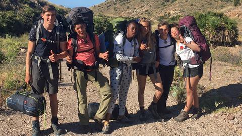 """Die """"Durch die Wildnis""""-Gruppe posiert fröhlich für ein Foto."""