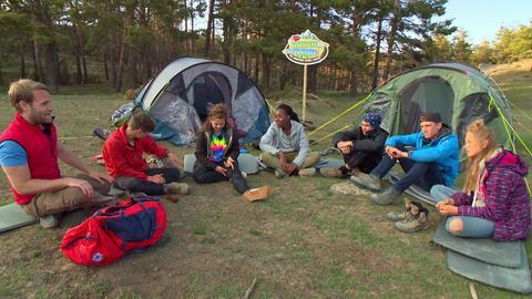 Die Jugendlichen sitzen mit Coach Tobi in einem Sitzkreis vor ihren Zelten.