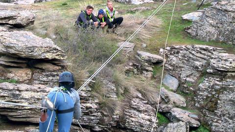 Drei Jugendliche beobachten, wie eine ihrer Mitstreiterinnen am Seil im Gebirge balanciert.