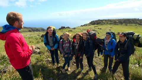 Die sechs Jugendlichen stehen oben auf einem Berg und lassen sich etwas von ihrem Coach erklären. Es ist windig.