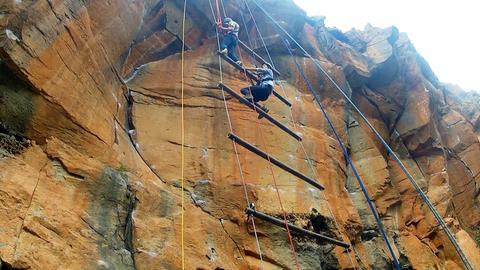Zwei Jugendliche klettern gesichert in einer Schlucht.