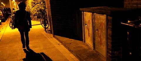 Eine Frau läuft auf einer dunklen Straße.