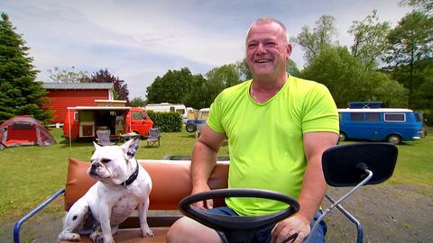 Sven Bettermann sitzt mit seinem Hund auf einem motorbetriebenen Wagen.