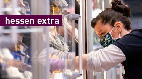 Eine Mitarbeiterin räumt im Supermarkt ein Tiefkühlfach ein.