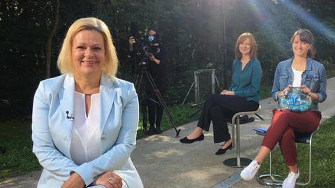 Nancy Feaser sitzt im Vordergrund unter einem Scheinwerfer. im Hintergrund zwei Interviewerinnen sowie eine Kamerafrau
