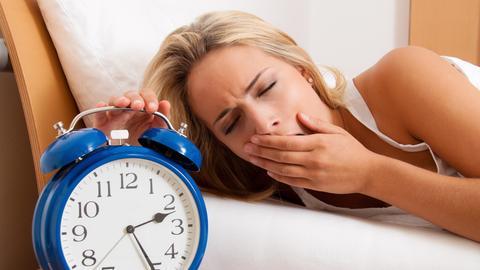 Eine gähnende Frau im Bett mit blauem Retro-Wecker