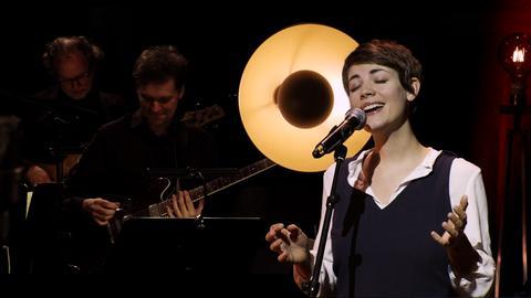 Musiker der Big Band im abgedunkelten Hintergrund. Rechts im Bild die singende Künstlerin Fee am Mikrofon.