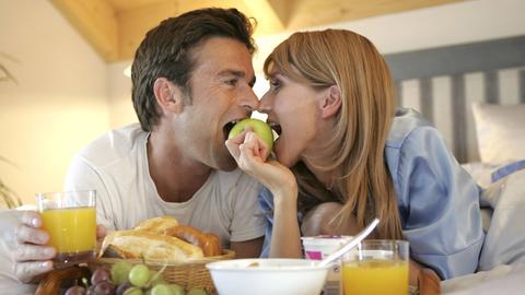 Ein verliebtes Paar liegt bäuchlings mit Frühstückstablett im Bett und beißt von beiden Seiten in einen grünen Apfel.