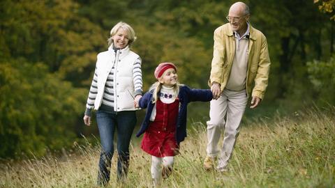Großeltern gehen mit ihrer Enkelin im Wald spazieren. Alle drei sehen glücklich und fit aus.