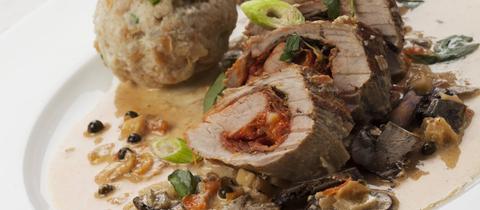 Drei Scheiben gefülltes Schweinefilet mit zwei Semmelknödeln auf einem Teller.