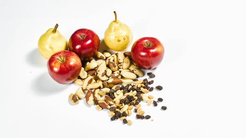 Eine Handvoll Nüsse und Rosinen und mehrere Äpfel und Birnen auf einer weißen Fläche.