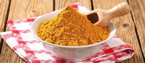 Ein Schüsselchen voller Currypulver mit einem kleinen Messlöffel aus Holz.