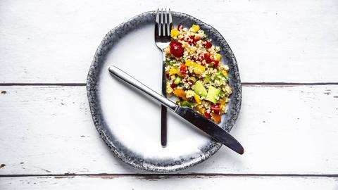 Bulgursalat mit Messer und Gabel auf einem Teller angerichtet. Messer, Gabel und Essen wurden so drapiert, dass es aussieht, als wäre es 16 Uhr (Messer und Gabel sind die Uhrzeiger).