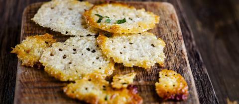 Selbstgemachte Parmesan-Chips auf einer Holzunterlage.