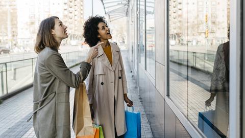 Zwei Frauen mit mehreren Einkaufstaschen in der Hand stehen vor einem Schaufenster und schauen begeistert hinein.