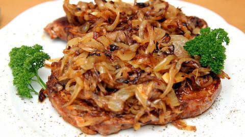 Ein saftiges Steak mit Zwiebeln und frischer Petersilie auf weißem Teller.