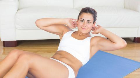 Eine Frau macht Sit ups auf einer Matte vor ihrer Couch.