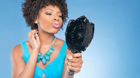 Eine junge Frau schaut zufrieden und selbstbewusst in einen Handspiegel und macht einen Kussmund.