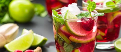Üppig gefülltes Glas Himbeere Mojito Cocktail mit Limette, Minze und Eis.