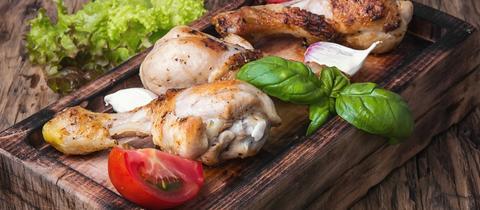 Gebratene Hähnchenkeulen auf einem stylishen Holzbrett, garniert mit Basilikum, Tomaten- und Knoblauchstücken.
