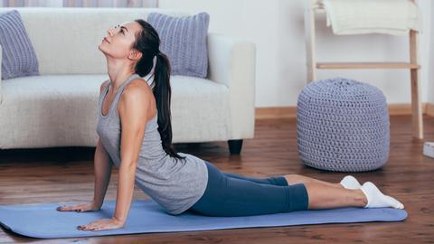 Eine junge Frau macht auf ihrer Yogamatte auf dem Holzboden eine Dehnübung.
