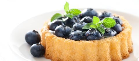 Heidelbeer-Tartelette auf einem weißen Tellerchen, garniert mit frischer Minze.