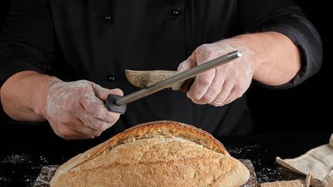 Ein Mann schleift über einem weißen Brot ein mit Mustern verziertes Messer.