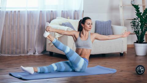 Junge Frau sitzt im Wohnzimmer auf ihrer Yogamatte und macht eine Yoga-Übung.