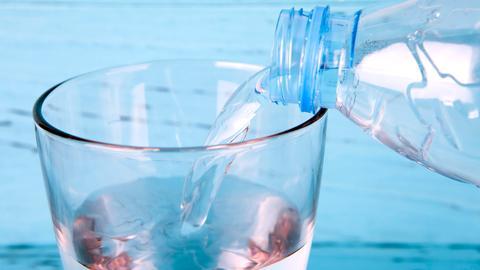 Aus einer Plastikflasch gießt jemand stilles Wasser in ein Glas.
