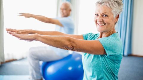 Ein älterer Herr und eine ältere Frau balancieren auf ihren Gymnastikbällen. Die Dame lächelt in die Kamera.
