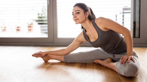Eine junge Frau stretcht sich.