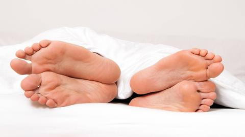 Die Füße eines Paares schauen unter der Bettdecke hervor. Aufrgund ihrer Position liegt das Pärchen Rücken an Rücken beieinander.