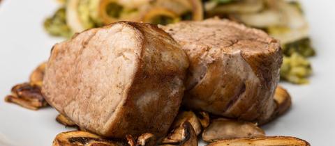 Zwei Stück Schweinefilet auf einem Teller, im Vordergrund kleingeschnittene Pilze.