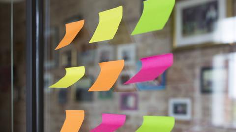 Neun bunte Post-it-Zettel kleben an einer Glasscheibe.