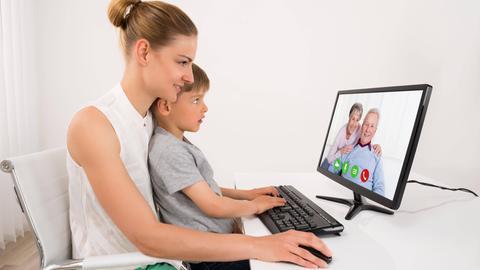 Mutter und Sohn führen ein Videotelefonat mit Oma und Opa.