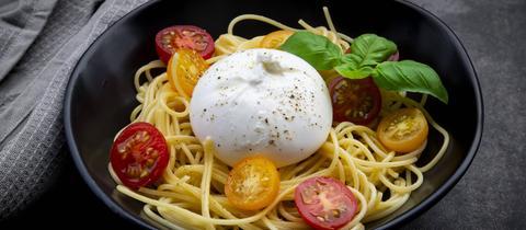 Ein Teller mit Spaghetti, frischen Tomaten und frischem Basilikum und einer Kugel Burrata obenauf.