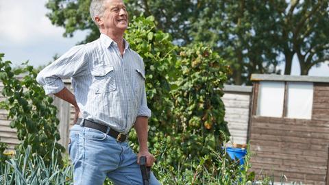 Ein älterer Mann mit schmerzverzerrtem Gesicht hält sich bei der Gartenarbeit den Rücken.