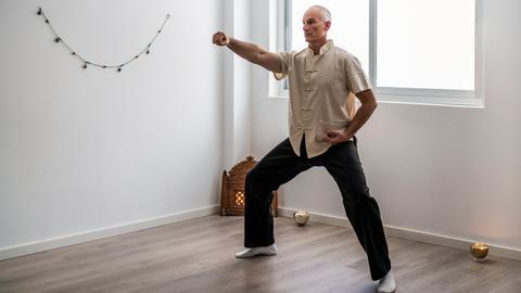 Ein älterer Mann praktiziert eine Qi-Gong-Übung.