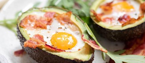 Die Hälfte einer überbackenen Avocado mit Ei und Speck.