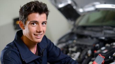 Kraftfahrzeugmechatroniker mit PKW im Hintergrund