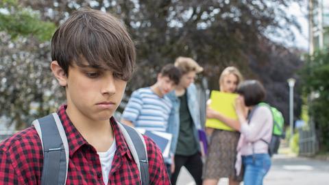 Trauriger Jugendlicher, der von einer Gruppe ausgeschlossen wird.