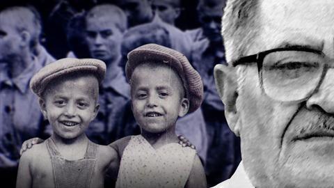 Ernst blickender Protagonist im Vordergrund. Ebenso zwei lachende kleine Jungen (schwarz-weiß-Fotografie). Im Hintergrund unscharf Gefangene von Auschwitz.
